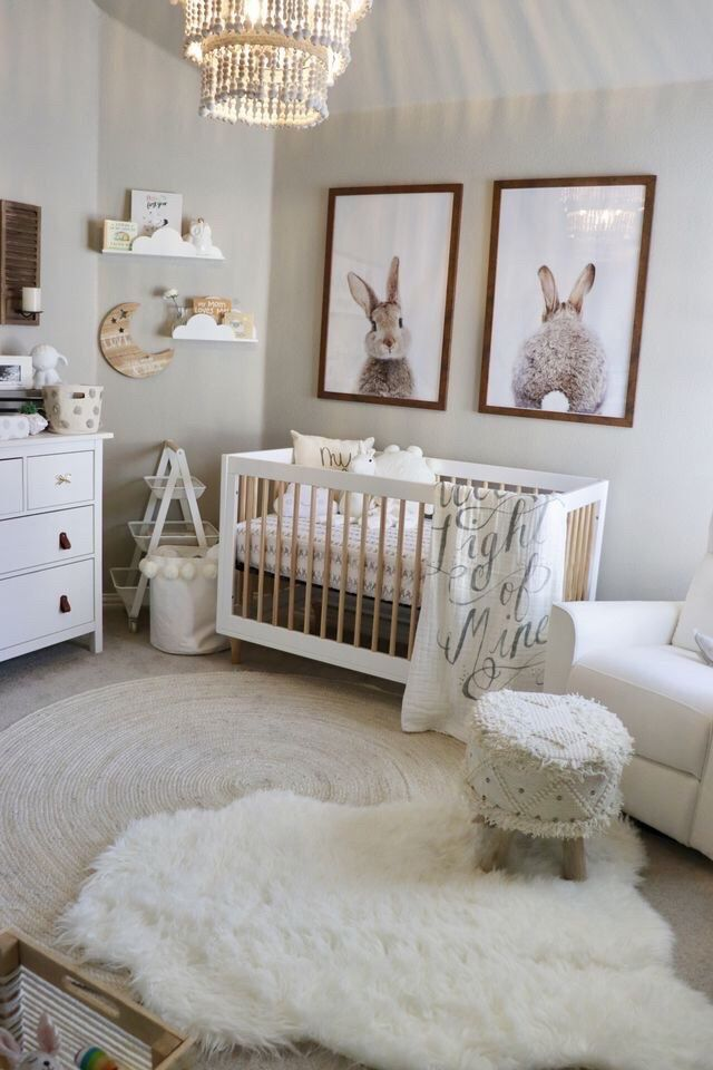nursery, gey floor, round rug, white fur rug, white ottoman, white chair, white wooden crib, white wall, white cabinet, rabbit's pictures