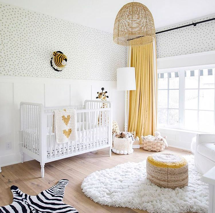 nursery, wooden floor, white rug, white wall, animal's decorations, yellow curtain, ottoman, baskets, rattan cover pendant