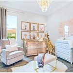Nursery, Wooden Pattern Floor, Modern Side Table, Pink Chair, Pink Ottoman, Pink Crib, Blue Cabinet, White Wall, Chandelier, Stuffed Giraffe, Animals' Paintings