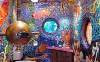 ocean bathoom, purple floor, mosaic tiles on ceiling wall depicts ocean, yellow tub, golden submarine tool, purple vanity