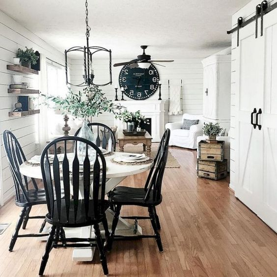 open dining room, wooden floor, white wooden planks wall, white round table, black chairs, white sofa, wooden coffee tbale, fireplace
