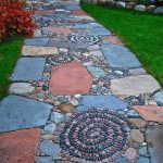 Pathway With Mosaic Soft Colored Tiles, Stones, Peebles, Surrounded By Green Grass, Plants