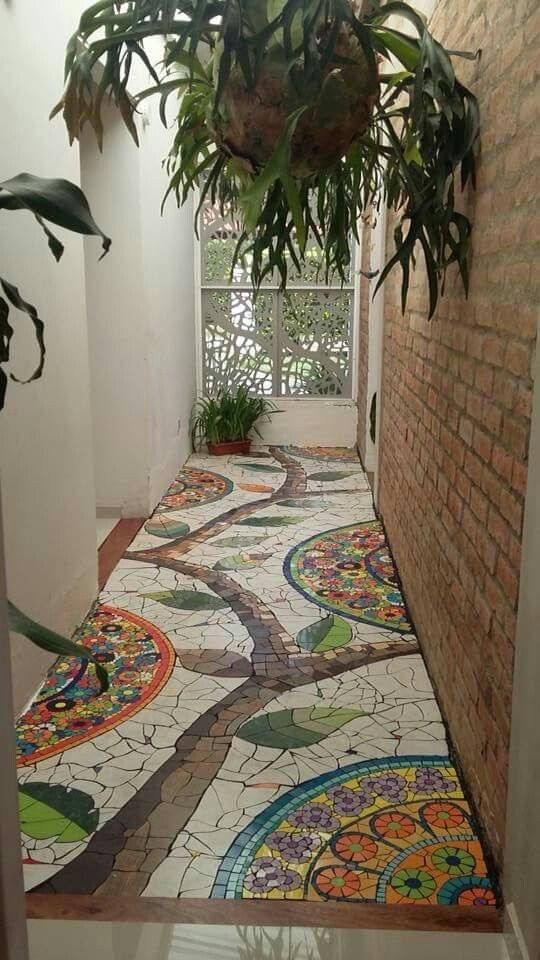 pathway with white tiles, colorful patterns, branch patterns, open brick wall on  one side, white wall, plants