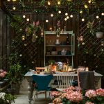 Patio, Wooden Floor, Wooden Exterior Wall, Wooden Racks Of Flowers, Cabinets, Wooden Table With Several Different Chairs, Plants On The Racks And Ceiling