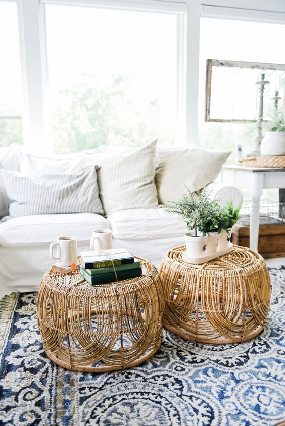 rattan round coffee table with pattern, blue rug, white soda, white wall