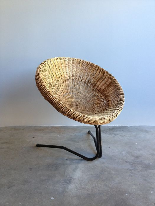 rattan woven chair with two metal legs on the front to the back