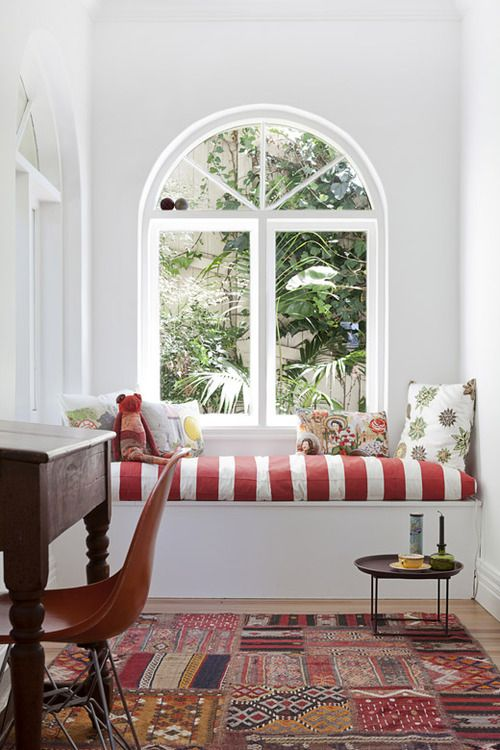 reading nook, white wall, white red stripes cushion, red patch rug, wooden floor, wooden study, brown chair