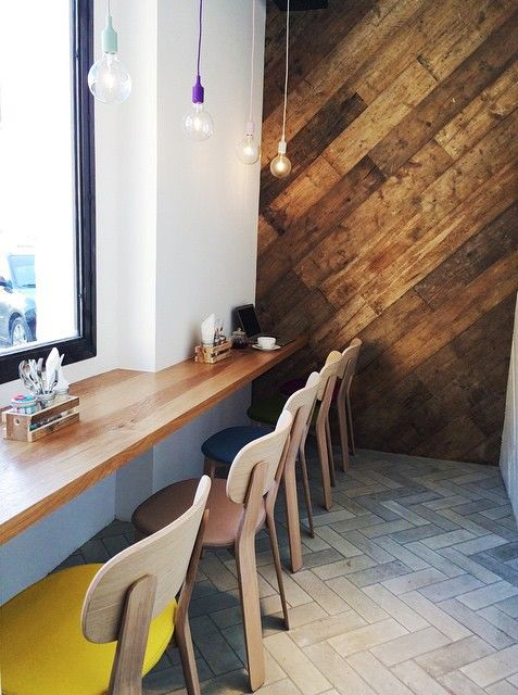 reclaimed wood accent wall, wooden chevron floor tiles, wooden long floating table, wooden chairs, white painted wall, colorful bulub pendants