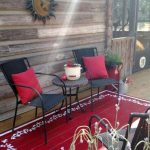 Red Painted Area Rug On Wooden Deck Under Black Chairs And Table With Red Pillows