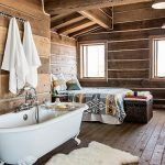 Rustic Bedroom With Wooden Floor, Wooden Wall, White Tub, Wooden Beams On Ceiling, Colorful Bedding