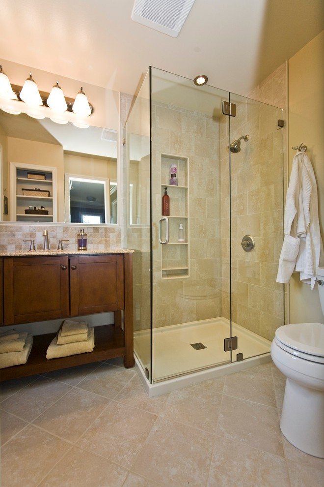 shower components beige wall and floor tiles glass shower enclosure built in shelves mirrored cabinet wooden vanity sink faucet toilet wall sconce