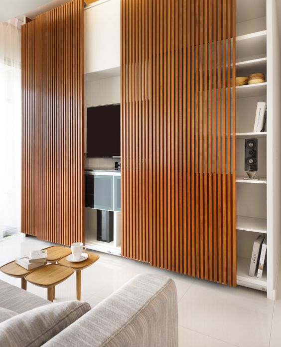 sliding wooden slats on white entertainment shelves, white floor, grey sofa, small coffee tables
