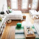 Small Apartment, Wooden Floor, Rug, White Sofa, White Bed, White Long Shelves Under TV, White Dining Table Wet, Large Windows, Open Brick Wall