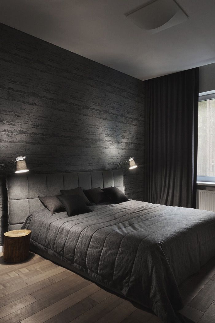small bedside sconces, black bedding, black wall. wooden floor