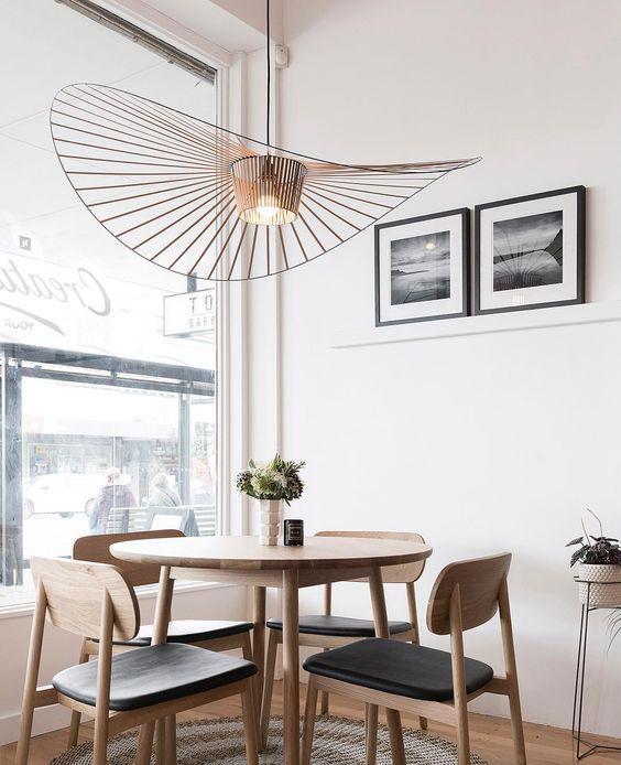 small dining set with round table and black seat wooden chairs, wooden floor, round rug, white wall, pendant with large round wing
