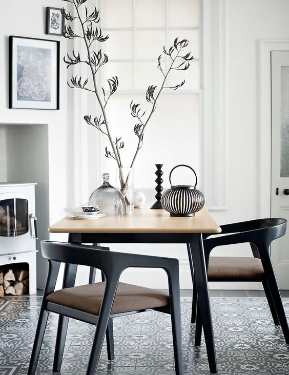 small dining set with small square table, black modern chairs in a room with white wall, patterned floor