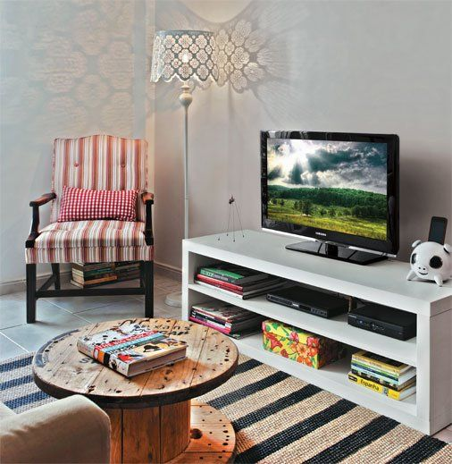 small living room, grey floor tiles, rattan stripes rug, round barrel coffee table, white shelves with TV, floor lamp, stripes chair