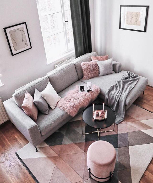 small living room, wooden floor, grey corner sofa, round pink otoman, black coffee table, pink geometric rug, white wall