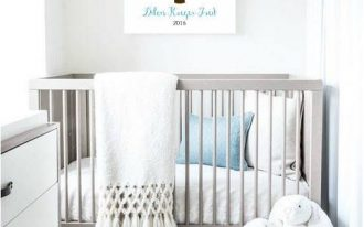 small nursery, white rug, light grey cot, white light grey cabinet, white woven basket, white wall