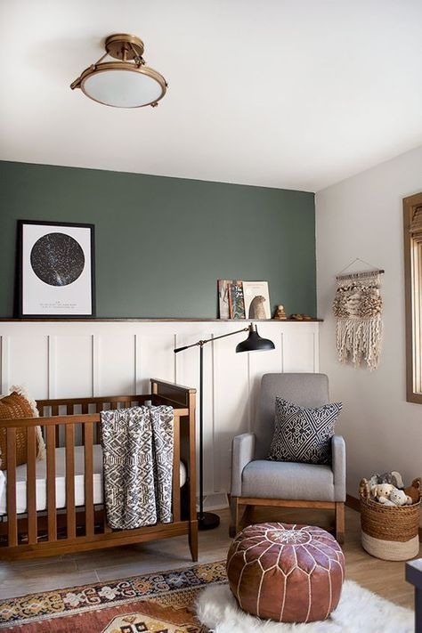 small nursery, wooden floor, rug, leather ottoman, grey chair, white wall, white molding wall, green wall, wooden cot, ceiling lamp