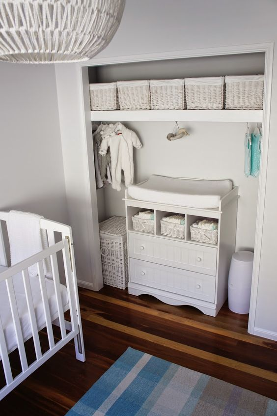 small nursery, wooden floor, white cot, blue rug, built in nook for cabinet, shelves, storing baskets