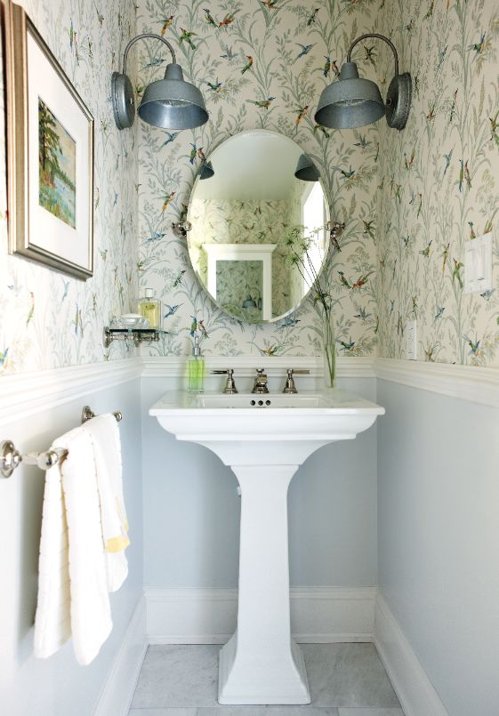 small powder room, blue painted half bottom, flowery wallpaper half top, round mirror, silver sconces, white sink, grey floor