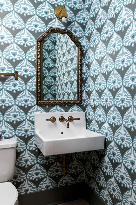 small powder room, blue wallpaper, white sink, white toilet, golden framed mirror, sconce