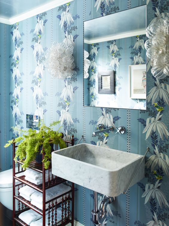 small powder room, blue wallpaper with white floer, white toilet, white marble sink, red metal shelves