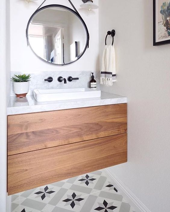 small powder room, floating wooden drawers with marble top, white square sink, black faucet, round mirror with black frame, black holder, patterned floor