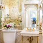Small Powder Room, White Molding, White Sink With Golden Support, White Toilet, Yellow Flowery Wallpaper, Big Mirror On The Wall, Golden Faucet, White Toilet, Traditional Chandelier