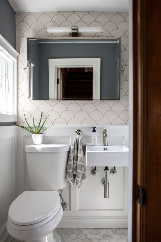 small powder room, white wainscoting, white hexagon floor tiles, grey wall, fish skin accent, white toilet, shite sink, mirror, white LED