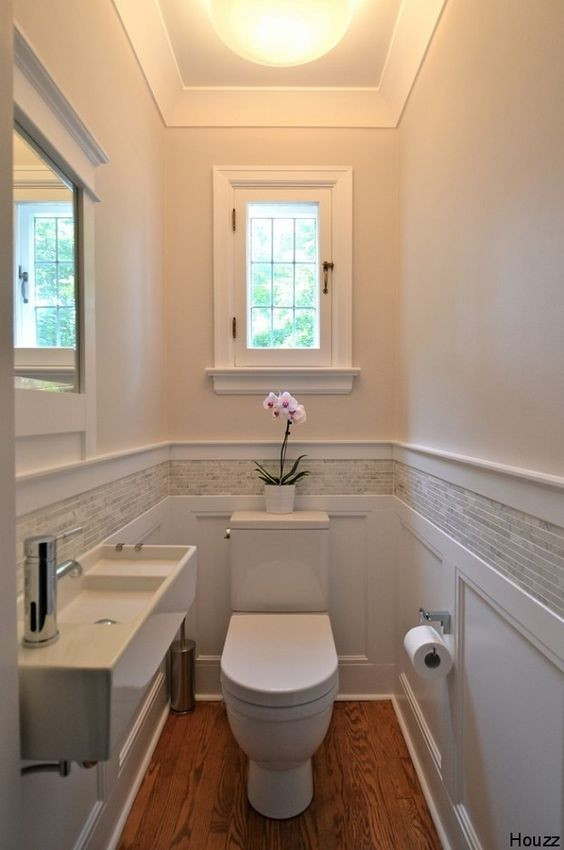 small powder room, wooden floor, wainscoting, short backsplash along the room, white wlal, ceiling lamp, mirror, white toilet