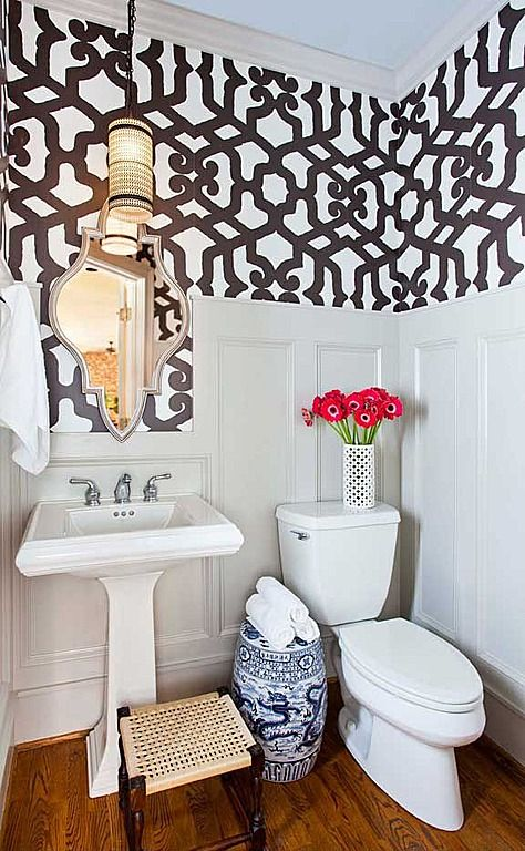 small powder room, wooden floor, white wainscoting, wallpaper, moroccan mirror, pendant, white toilet, white sink, oriental vase, rattan stool