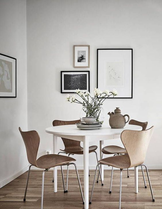 small round white dining table with brown modern chairs, white wall, wooden floor