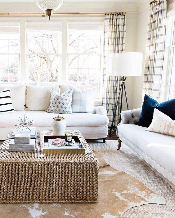 square rattan coffee table, rug, white sofa, white floor lamp, white wall, pillows, plaid curtain