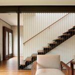 Steel Stair Detail Big Black Standing Decoration Wooden Floor Woden Chairs With Beige Cuhions Glass Front Doors Concrete Walls