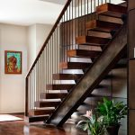 Steel Stair Detail Big Steel Wooden Steps Indoor Plants Wooden Stairs Cap Colorful Artwork White Walls Wooden Accent Wall Wooden Flooring Area Rug
