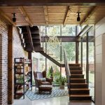 Steel Stair Detail Glass Windows Wooden Steps Candelier Ceiling Lamps Steel Book Rack Brown Leathered Armchairs Leathered Stools Area Rug Wooden Ceiling