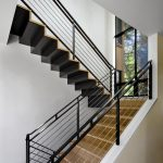 Steel Stair Detail Wooden Stairs Black Steel Caps Thick Cable Railing White Walls Glass Windows Black Steel Framed Glass Windows