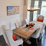 Studded Dining Chair Altar Chandelier Wooden Dining Table Hard Wood Flooring Glass Windows Beige Walls Artwork Colorful Curtains Orange Pillows