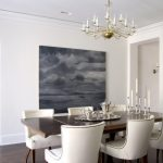 Studded Dining Chair Chandelier Grey Artwork White Walls Wooden Dining Table Silver Ware Standing Floor Mirror Glass Window Roman Shade