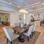 Studded Dining Chair Chandelier Wooden Dining Table Traditional Rug Wooden Floor Island Pendant Lamps Glass Windows White Cabinets