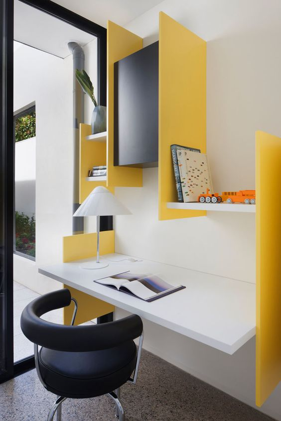 study area, grey marble floor, white wall, white floating table, yellow partition shelves, black round office chair, black cabinet, white table lamp