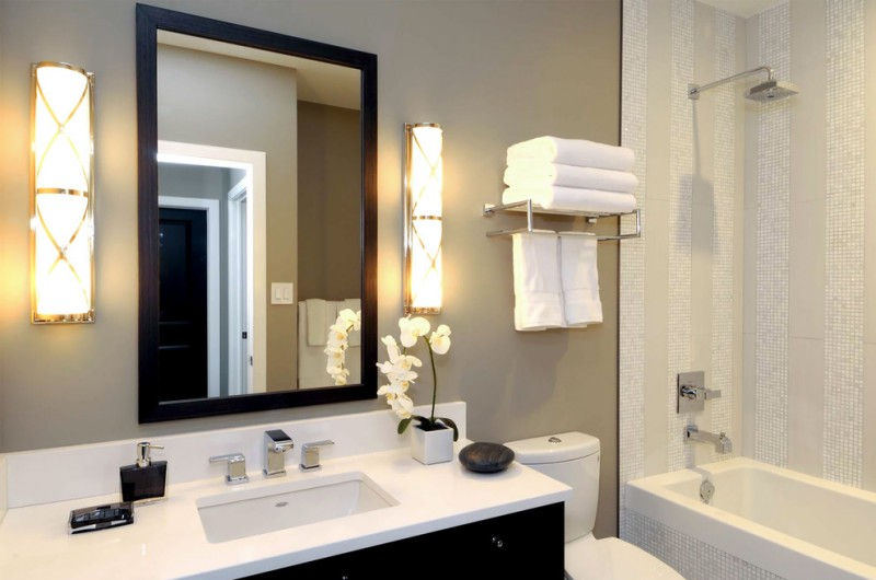 towel rack height wall sconces wall mirrors shower head built in tub black vanity white sink faucet mosaic wall tiles toilet grey wall white countertop