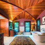 Unique Ceiling Wooden Ceiling Acrylic Freestanding Tub Wall Sconce Wooden Vanity Glass Windows Window Blinds Bathroom Rug White Tiles Mirror Chair