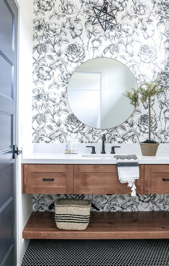 vanity with wooden floating drawers, floating shelves, white top, black faucet, round mirror, flowery wallpaper