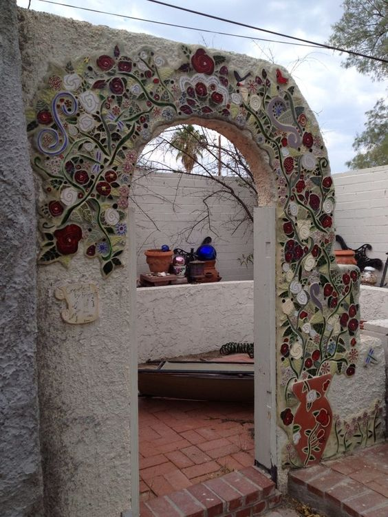 white arch with red, white flowers on orange pot carved
