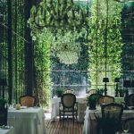White Dining Table, Wooden Rattan Chairs, Glass Wall, Plants Outside, Chandeliers