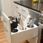 White Drawers Cabinet Under Black Marble Top With Built In Holes For Kitchen Tools