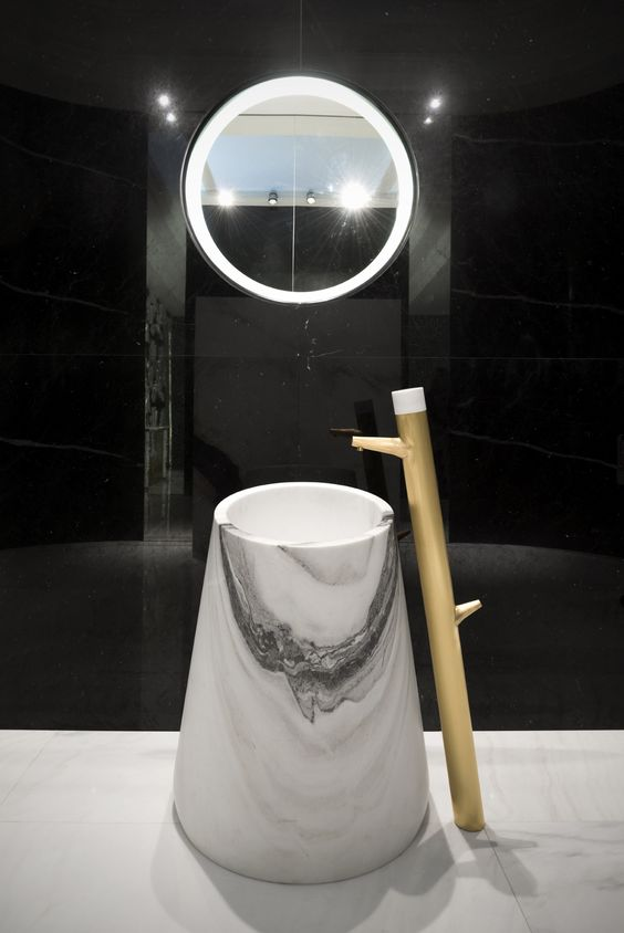 white marble tall round sink with brown faucet from the floor, white framed mirror, white floor, black wall tiles